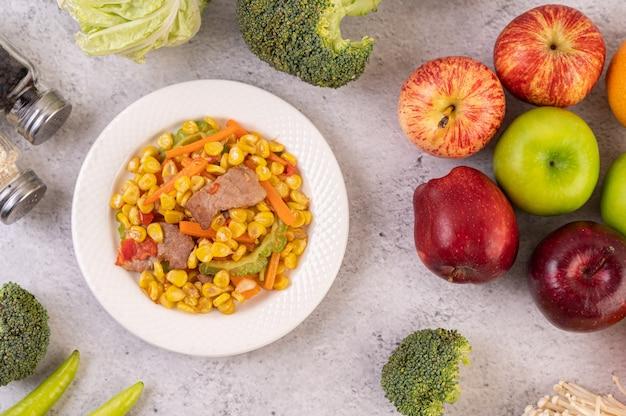 옥수수와 당근을 저어주고 나무 접시 위에 돼지 고기를 접시에 담습니다.