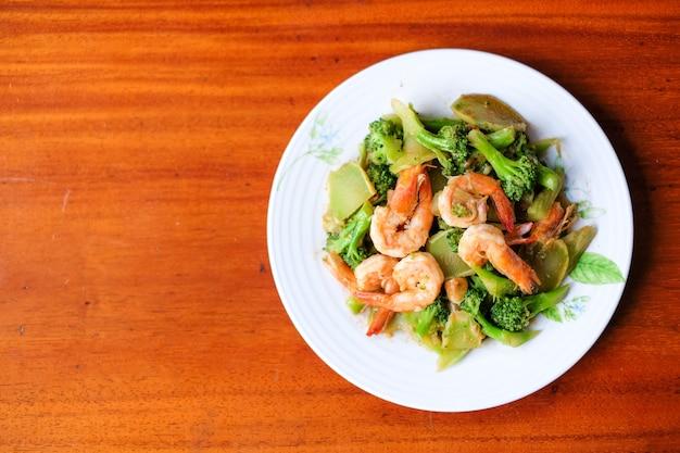 Горячий stir зажарил брокколи с гигантской подачей креветки на тарелку - концепцию еды.