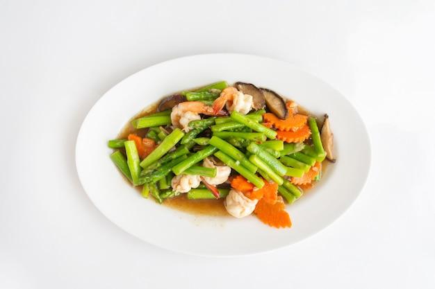 Stirfried смешанные овощи, спаржа, грибы и креветки на белом столе. тайская местная кухня.