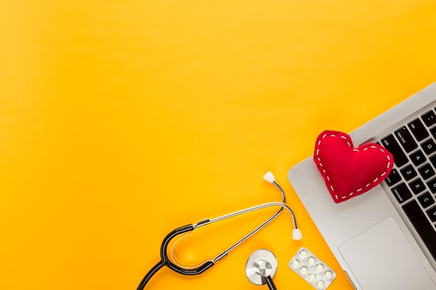 Stitched heart shape on laptop with stethoscope; blister packed tablet on yellow background