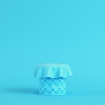 パステルカラーの明るい青色の背景に生地で覆われたステッチ台座