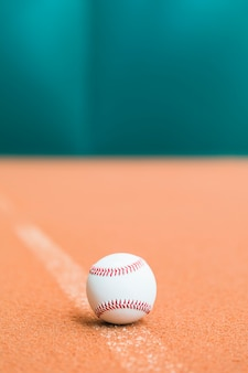 Stitched white baseball on pitch