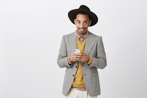 Stlylish african-american man in suit using smartphone and listening music in earphones