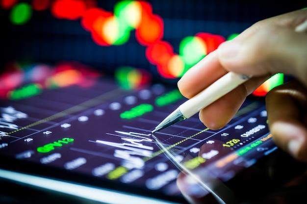 디지털 태블릿과 손으로 가리키는 주식 분석