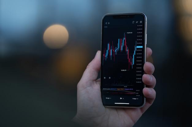 Фондовая биржа и торговля в интернете. мужская рука держит смартфон и использует инвестиционное приложение, анализируя рыночные данные в режиме реального времени. выборочный фокус на мобильном телефоне с финансовой диаграммой на экране