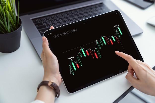 証券取引所への投資、ハンドプレスデジタルタブレット、および職場の取引グラフ。市場価値を評価します。