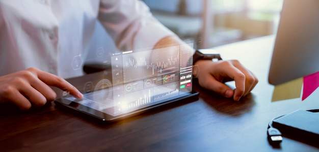 証券取引所市場の概念、実業家の手トレーダープレスデジタルタブレットグラフ分析キャンドルラインオフィスのテーブル、画面上の図。