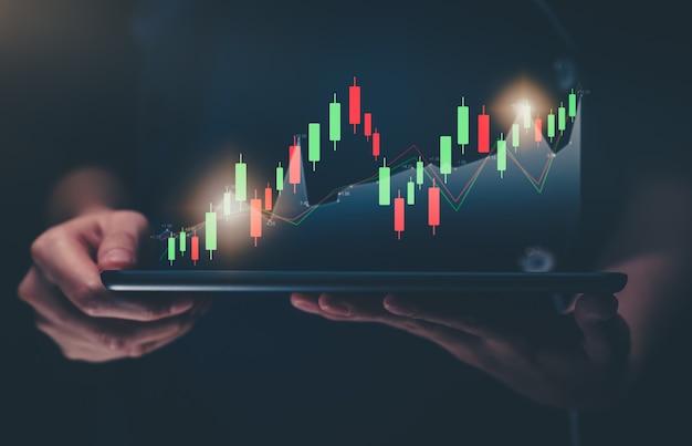 증권 거래소 시장 개념, 그래프 분석 촛불 선이 있는 디지털 태블릿을 손에 들고 보케 색상 조명.