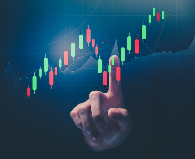 증권 거래소 시장 개념, 손으로 화면을 가리키며 그래프 분석 촛불 선이 보케 색상 조명에 표시됩니다.