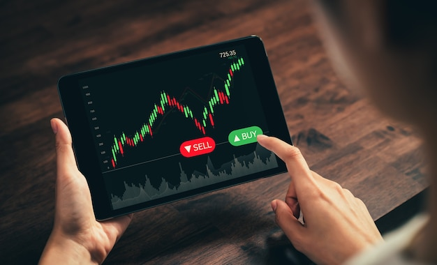 Stock exchange market concept, hand trader touch on digital tablet with graphs analysis candle line on the table in office, diagrams on screen.
