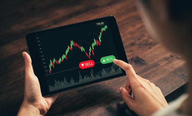증권 거래소 시장 개념, 사무실의 테이블에 그래프 분석 촛불 선, 화면의 다이어그램이 있는 디지털 태블릿에 손 거래자가 터치합니다.