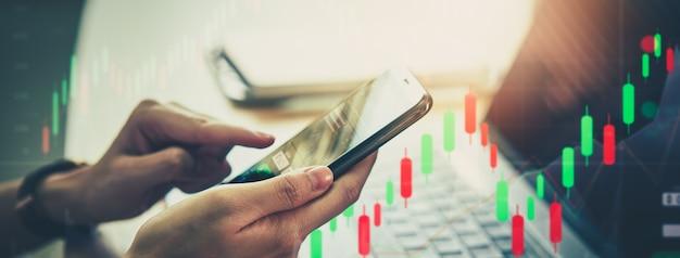 증권 거래소 시장 개념, 스마트폰을 사용하여 그래프 분석 촛불 선을 보케 색상 조명에 사용합니다.