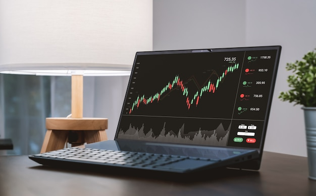 Stock exchange market concept, laptop show graphs analysis candle line screen on the table.