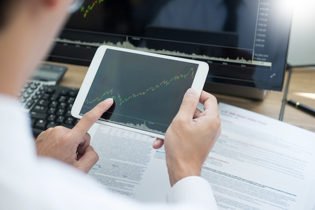 Stock exchange trader analyzing graphs chart or data on multiple screens in office.