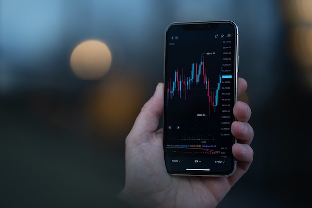 Stock exchange and trading online. male hand holding smartphone and using investment app, analyzing market data in real time. selective focus on mobile phone with financial graph chart on screen