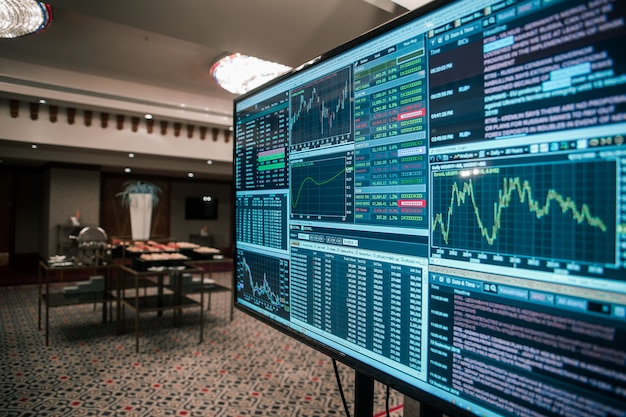Stock growth on a monitor in a business hall exchange chart invest