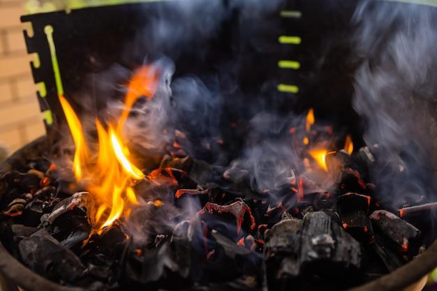 炭火グリルのストックイメージ、ライブ炎でクローズアップ。 Premium写真