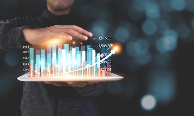 Инвестор запаса держа таблетку которая показывая диаграмму и диаграмму виртуальной фантазии технические с стрелкой. бизнес прибыль и концепция роста дивидендов.