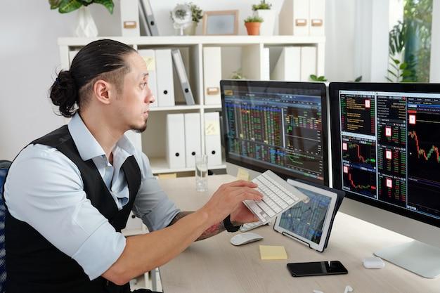 Брокер на фондовом рынке, торгующий онлайн в современном офисе, покупка и продажа акций