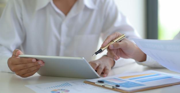 주식 시장 전문가는 태블릿을 사용하여 변동성 주식 시장 상황을 평가하기 위해 뉴스를 따릅니다.