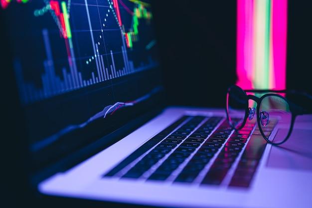 ノートパソコンの画面上の電子ボード上の株式市場グラフの財務データ