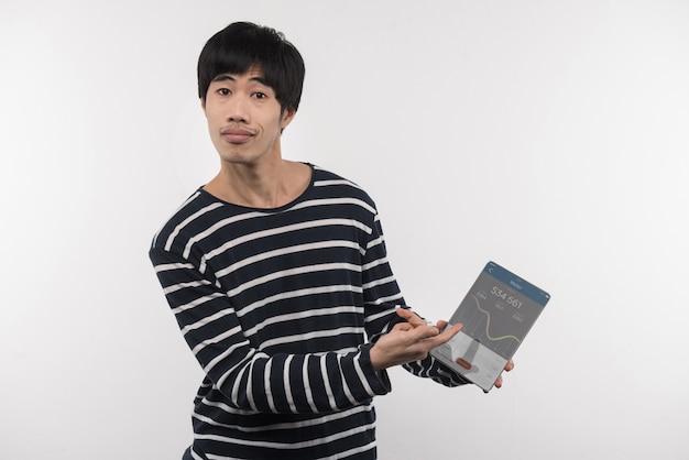주식 시장. 주식 시장에서 작업하는 동안 태블릿 화면에서 가리키는 좋은 아시아 사람