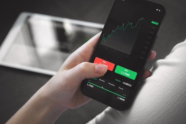 自宅での株式市場取引。投資、売買のための財務グラフ付きの携帯電話を使用している人