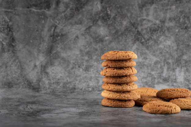 A stock of oatmeal cookies on grey concrete.
