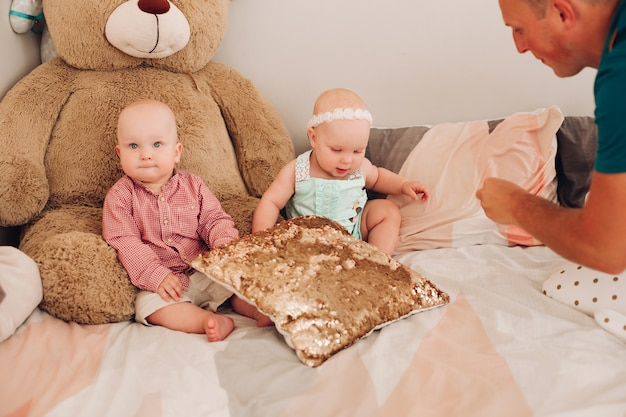 Stock photo of adorable kids - sister and brother - sitting on bed with big teddy bear. dad playing with two cute babies on the bed.