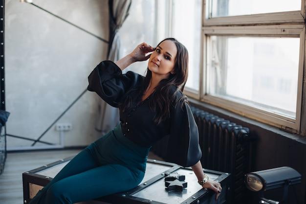 Foto di stock di attraente bruna giovane donna adulta in camicetta nera e pantaloni verde scuro in posa contro il muro bianco con molte lampade.