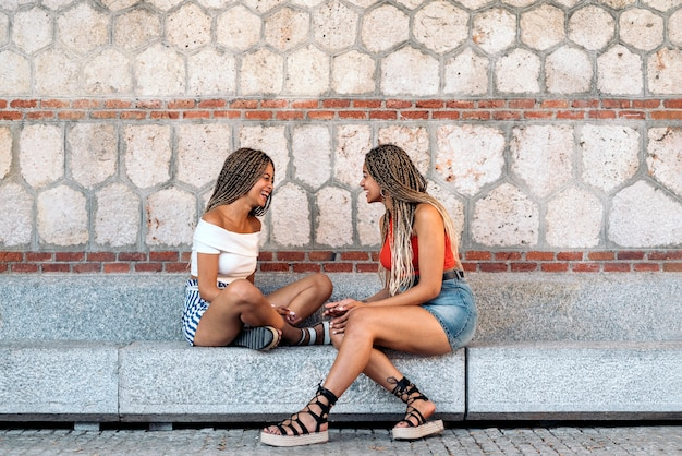 Stock photo of beautiful african american sisters laughing and looking at each other while sitting in the street.
