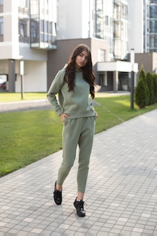 Stock photo of a beautiful young woman in olive sportive suit and black sneakers walking with hands in pockets. trendy model in sportsuit with joggers and hoodie walking inthe street. Free Photo