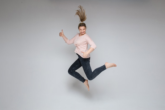 Stock photo of cheerful carefree blonde woman jumping in mid-air with thumbs up on white background. jumping woman smiling at camera holding thumbs up.