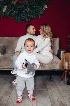 Stock photo of cute little toddler with toy dog standing on floor against loving parents on sofa.