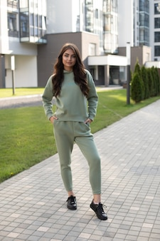 Stock photo of a fashion young model with long wavy hair wearing stylish sweatshirt and joggers with black leather shoes standing in modern street with contemporary buildings.