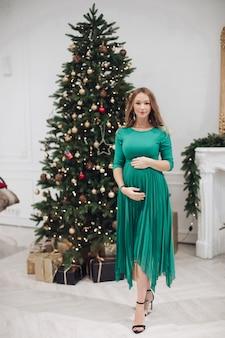 装飾されたクリスマスツリーの前に立って、カメラに微笑んで彼女の腹を抱き締めるお祝いの緑のドレスで見事な妊婦の完全な長さのストックフォト。スタジオショット。クリスマスのコンセプト。