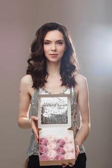 Foto di stock di splendida donna bionda che tiene presente con i dolci. isolato su sfondo grigio.