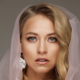 Stock photo of a gorgeous blonde woman with blue eyes and natural make-up wearing pink veil and holding fragile pink rose. bride concept.