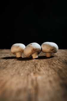 Stock photo of group of mushrooms on wooden table and black background.