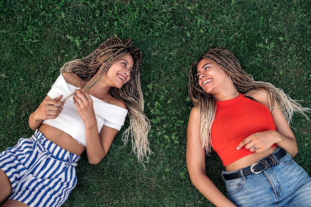 Stock photo of happy african american sisters with cool braids having fun and lying on the grass.