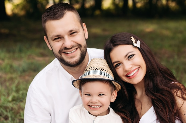 스톡 사진 어머니, 아버지와 여름 날에 공원에서 카메라에 행복 하 게 웃 고 그들의 아들의 사랑스러운 백인 가족의 얼굴 만.