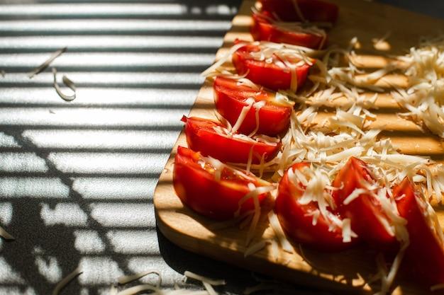 日光の下で木の板に細かく刻んだチーズとスライスしたトマトのクローズアップのストックフォト。テーブルの上のブラインドシャドウ。調理プロセス。