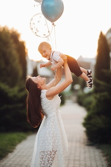Stock photo of a loving mother in beautiful white summer dress raising her son with inflatable air balloons in the air in lovely garden in blurred background. celebrating son s birthday outdoors.