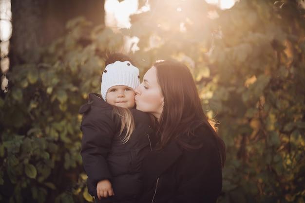 美しいブルネットの母親の頬に彼女の素敵な若い娘にキスのストックフォト。彼らはバックライト付きの秋の木々に対して森の中に立っています。