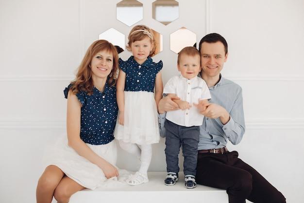 2人の子供(娘と息子)とカメラに微笑んでいる美しい白人家族のストックフォト。カメラに微笑んでいる2人の子供と家族のポーズ。