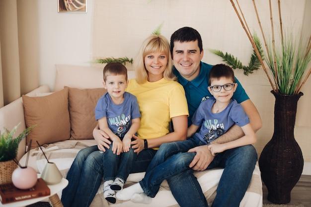 두 명의 미취학 아동이 아늑한 소파에 앉아 카메라를 보며 웃고 있는 아름다운 쾌활한 가족 사진. 아버지, 어머니, 그리고 두 아이가 함께 시간을 즐기고 있습니다.