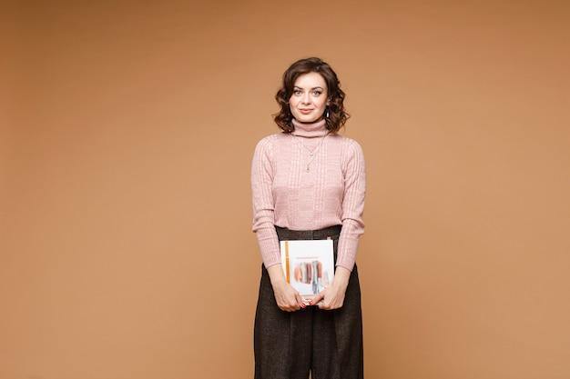 거북이 목과 책을 들고 짙은 갈색 바지와 밝은 분홍색 스웨터에 아름 다운 유행 갈색 머리 여자의 스톡 사진