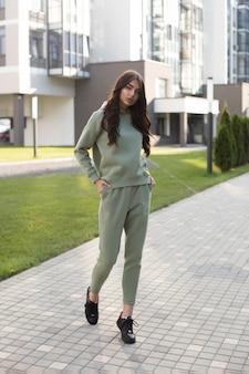 ポケットに手を入れて歩いているオリーブのスポーツスーツと黒のスニーカーの美しい若い女性のストックフォト。ジョギングやパーカーが通りを歩いているスポーツスーツのトレンディなモデル。
