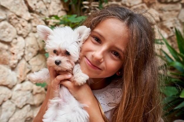 그녀의 얼굴 앞에서 그를 애무하는 작은 강아지와 함께 흰색 옷을 입은 금발 소녀의 스톡 사진