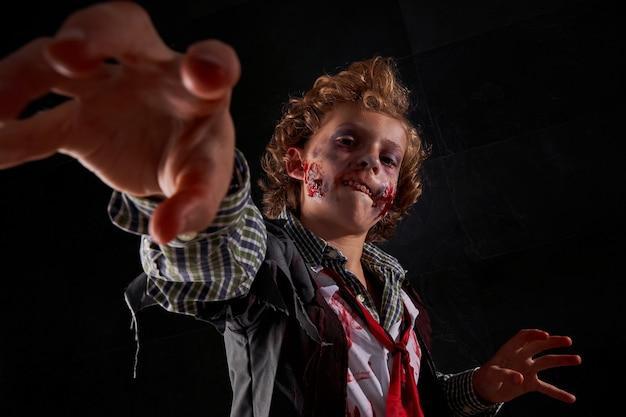 Стоковая фотография мальчика, замаскированного под зомби с поднятыми руками в крови, пытающегося поймать что-то впереди. хэллоуин